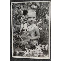 Фото девочки в цветах. 1960-е. 9х13 см