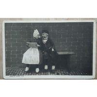 Старинная открытка. Мальчик и девочка на скамье. Подписана.